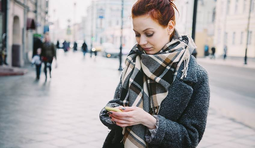Russian woman texting on her cell phone in the streets.